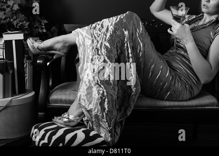 A young woman in an elegant formal gown reclines on a settee.  Black & white.  Only partial face is included making - Stock Photo