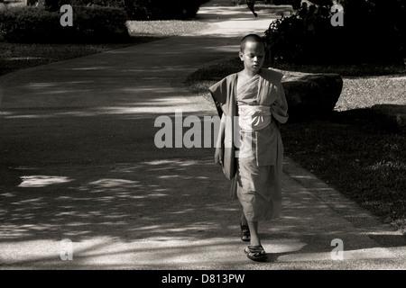PHUKET, THAILAND APRIL 28 2013: Novice monk vists Wat Chalong, the largest Buddhist temple in Phuket. - Stock Photo