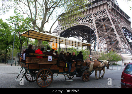 Horse chariot with passengers in front of Eiffel Tower, Paris, France - Stock Photo