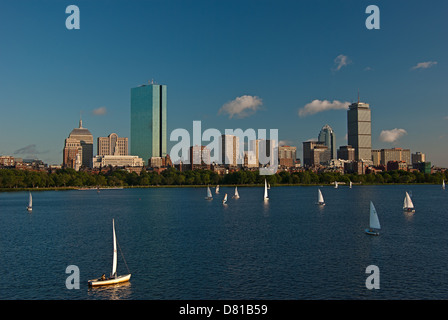 Sailboats seen on the Charles River illuminated by the afternoon sun with the Boston skyline in the background - Stock Photo