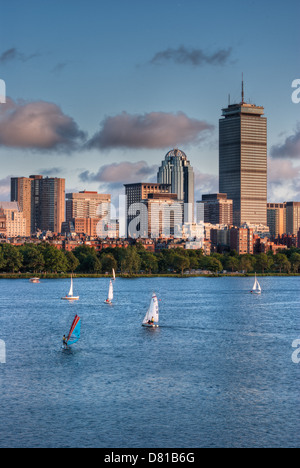Sailboats head toward the docks at sunset with a view of the Boston skyline in the background - Stock Photo