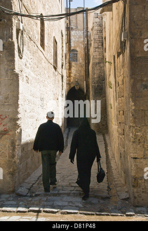 Aleppo Syria. A man and woman walking down a narrow old cobbled street in the old city centre, a UNESCO World Heritage - Stock Photo