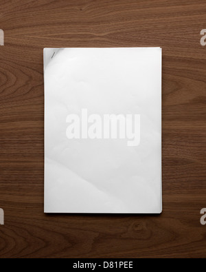 plain sheet of A4 paper with a stapled corner lying flat on a wooden table shot from above - Stock Photo
