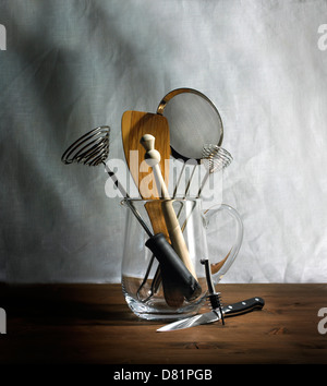 Kitchen utensils in glass jug cut out gray and brown background - Stock Photo