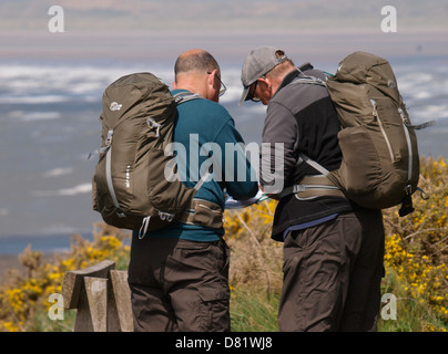 Two hikers checking the map, South West Coast Path, Devon, UK 2013 - Stock Photo