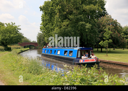 A narrowboat on the Staffordshire & Worcestershire Canal at Tixall with Tixall bridge in the background - Stock Photo