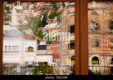 Reflection of war damaged building and new mosque in Mostar Bosnia Herzegovina - Stock Photo