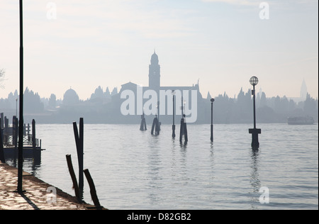 A misty atmospheric shot of a distant church tower in the Venice lagoon from Murano island Venice Italy - Stock Photo