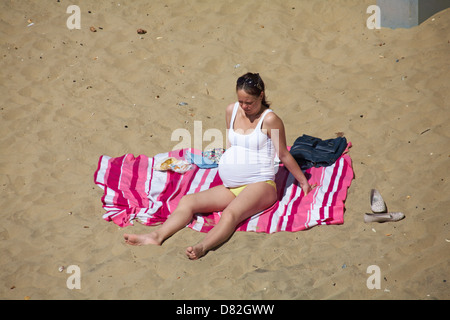 Heavily pregnant woman sunbathing on Bournemouth beach in May - Stock Photo