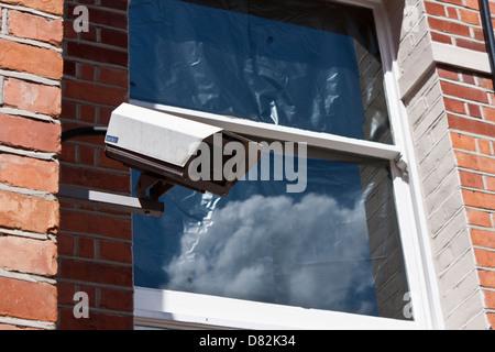CCTV surveillance camera on building outside window - Stock Photo