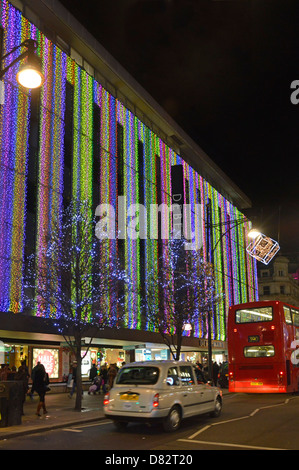 night view of Debenhams department store in Oxford street with Christmas lights taxi cab and bus - Stock Photo