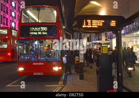 Bus stop shelter at night with people boarding London double decker bus with indicator board giving live arrival - Stock Photo