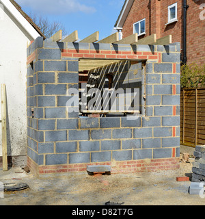 Two storey home bedroom extension under construction to side of a detached house block wall is new kitchen England - Stock Photo