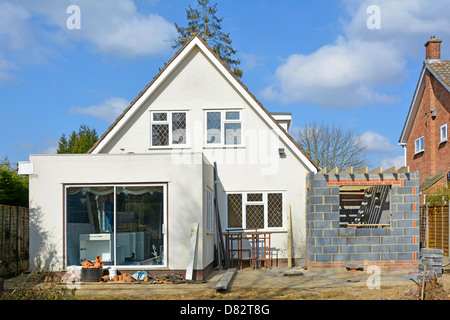 Building work to side of detached house to add two storey bedroom & kitchen extension seen from back garden England - Stock Photo