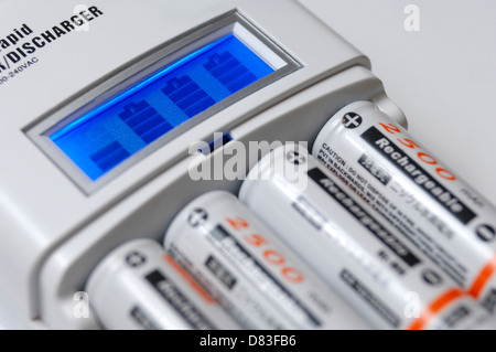 Smart rapid AA battery charger with LCD showing the charge level and four rechargeable NiMh batteries - Stock Photo