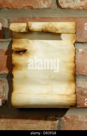 Old blank parchment with burnt edges on a red brick wall Grungy artistic background - Stock Photo