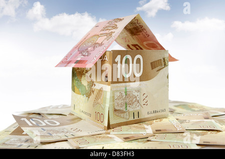 Model of a house made from Canadian dollar bills closeup Mortgage Investment Property insurance Property tax Banking - Stock Photo