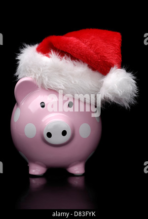 Piggy bank in Christmas hat isolated on black background - Stock Photo