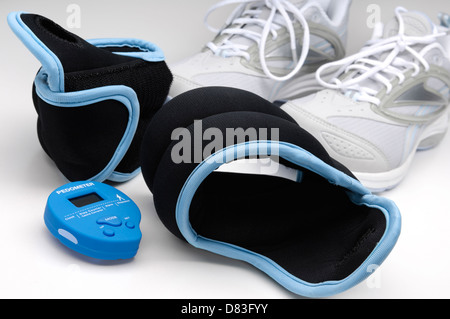 Exercise wrist weights, pedometer and running shoes still life - Stock Photo
