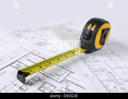 Tape measure on construction plans of a house - Stock Photo