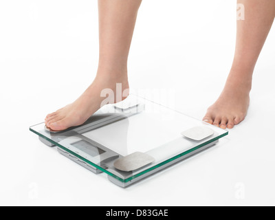 Closeup of woman legs stepping on weight scale. Isolated on white background - Stock Photo
