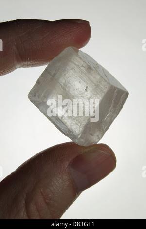 Clear Quartz Crystal Held Between Fingers - Stock Photo