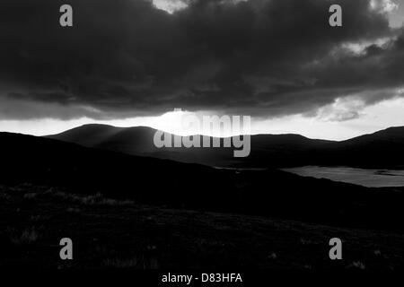 Rainy moody skies with sun poking through clouds over mountains giving hope and change for the future - Stock Photo