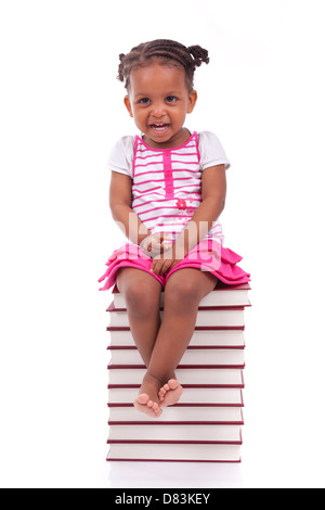 Cute black african american little girl seated in a stack of books, isolated on white background - African people - Stock Photo