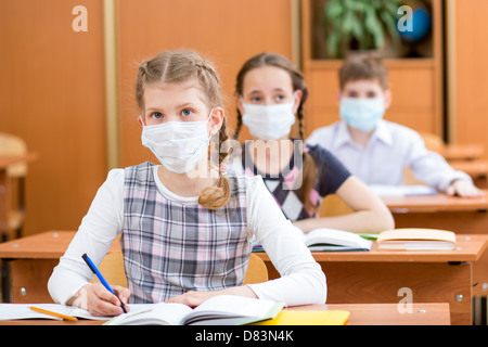 schoolkids with protection mask against flu virus at lesson - Stock Photo