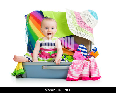 Baby girl sitting in suitcase with things for vacation travel - Stock Photo