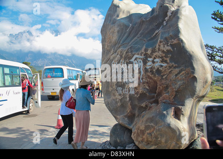 Tourists buses outside the Impression of Lijiang cultural performance dance stadium at Lijiang, Yunnan China - Stock Photo