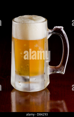 cold beer served in a frozen mug on a bar top isolated on a black background - Stock Photo