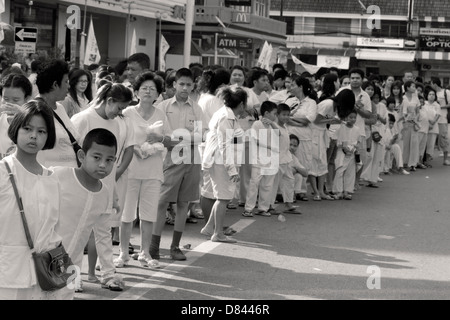 PHUKET, THAILAND OCTOBER 2 2011: Onlookers watch street procession during annual Phuket Vegetarian Festival - Stock Photo