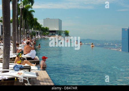 Guest of Marina Bay Sands Hotel Chilling by the Infinity Pool at the roof top soaking in the afternoon sun and sights - Stock Photo