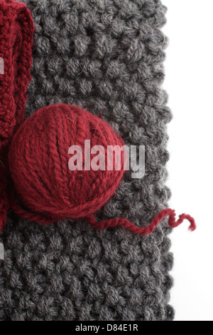 Knits and a ball of wool on a white background - Stock Photo