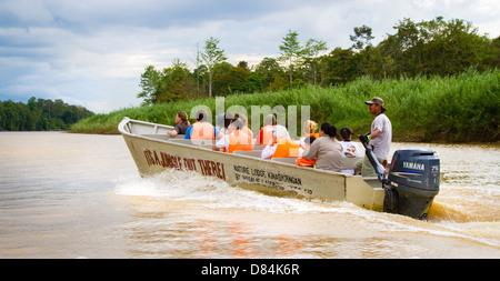 Tourists enjoying a wildlife safari on the Kinabatangan River in Sabah Borneo - Stock Photo