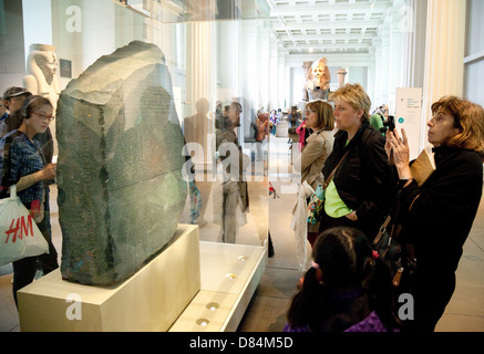 People looking at the Rosetta Stone, interior, the British Museum, london UK - Stock Photo