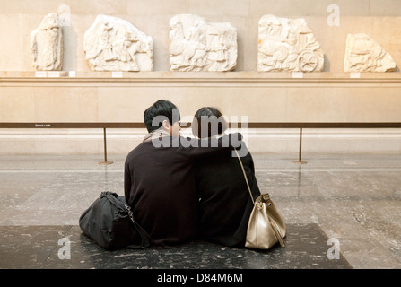 A couple in the Greek Gallery, seeing part of the Elgin Marbles, the British Museum, London UK - Stock Photo