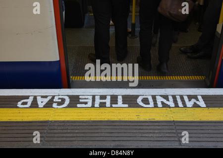 Mind the Gap sign on London Underground platform - Stock Photo