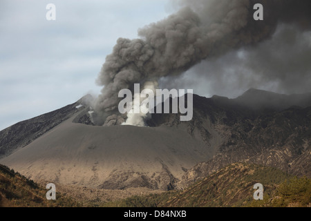 February 25, 2013 - Sakurajima volcano, Japan. Emission of ash from one vent while second vent emits steam. - Stock Photo