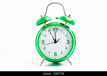 Picture of a green retro alarm clock on a white background with the clock five to twelve - Stock Photo