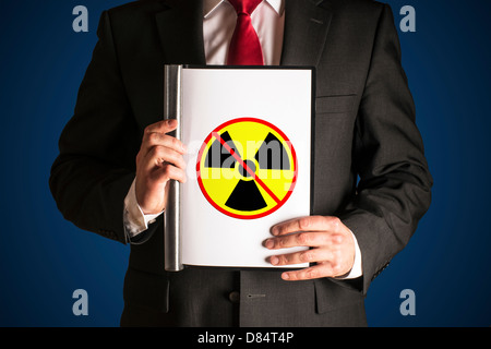 Man in black suite is holding a folder with sign no atomic power - Stock Photo