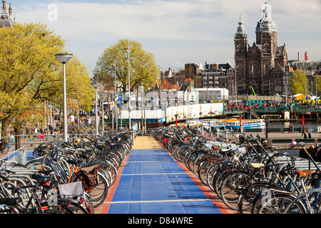 Bikes in bike racks in amsterdam, Netherlands. A huge percentage of the population cycle in this flat, low lying country.