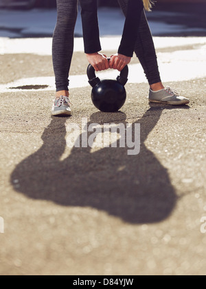 Outdoor fitness woman lifting a heavy kettle bell - Stock Photo