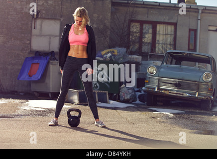 Ghetto girl with kettlebell in a crossfit training outdoor - Stock Photo