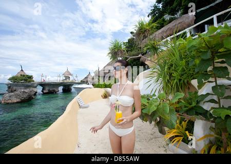 young woman glass orange juice ocean. - Stock Photo