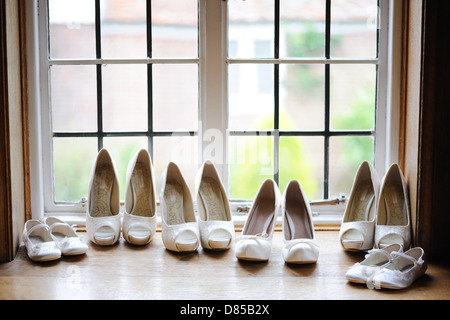 Bride and bridesmaids shoes in window - Stock Photo