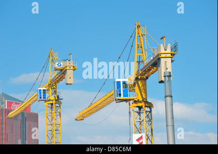 Two large yellow cranes visible above the Johannesburg skyline. - Stock Photo