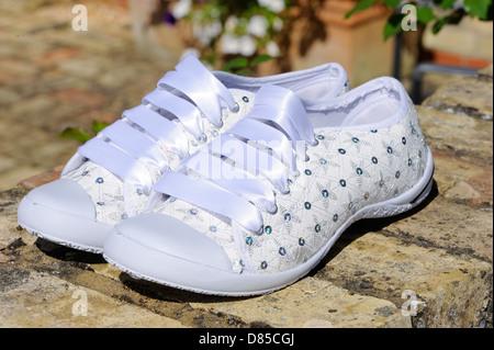 Brides white shiny sports shoes - Stock Photo