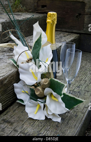 bridal flowers with champagne and glasses set on wooden steps - Stock Photo